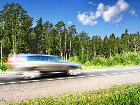 car speeding on country highway, blured in motion