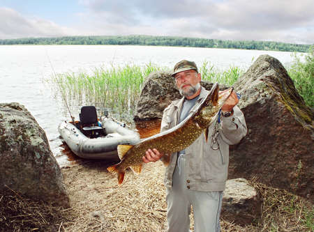 fishing tackle: angler catching big pike fish, fishing on lake with boat
