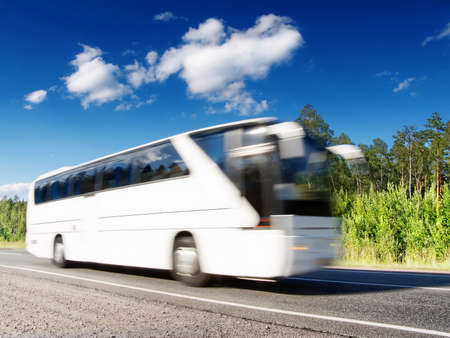 white tourist bus on summer country highway, blured in motion