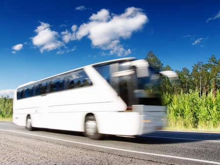 weiße Touristenbus auf Sommer Landstraße, Blured in Bewegung