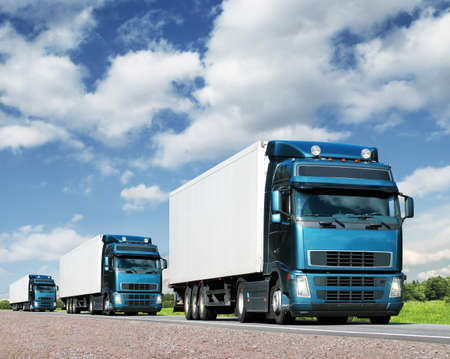 caravan of trucks on highway, cargo transportation concept Stock Photo