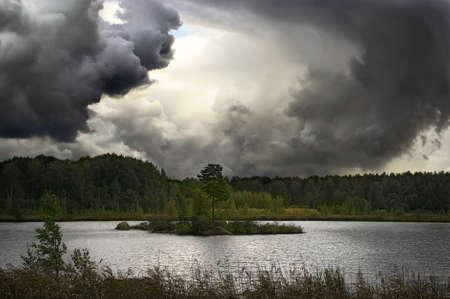 dragon shaped monster cloud swirl over lake island, tornado, thunderstorm Standard-Bild