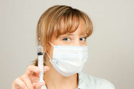 young girl doctor during the period of coronavirus in a medical mask with a syringe in his hands