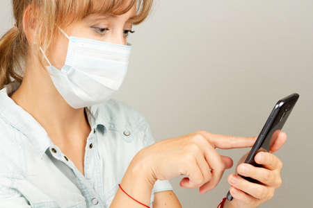 a young girl during the coronavirus pandemic in a medical mask with a smartphone in her hands
