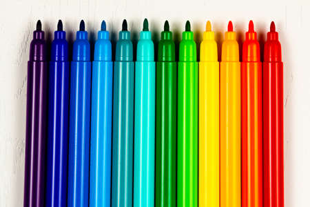 bright colored markers without caps lie on a white wooden table Stockfoto