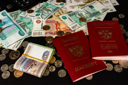 coins and paper money and two international passports lie on a black wooden table inscription passport Russian federation
