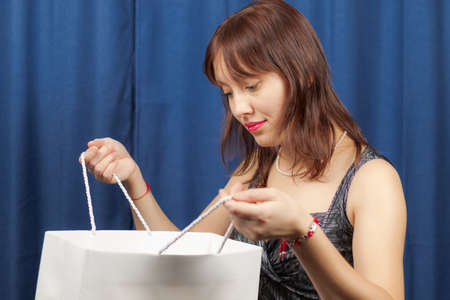 cute young brown-haired girl in a black and silver dress holding a white package with a gift on a blue background