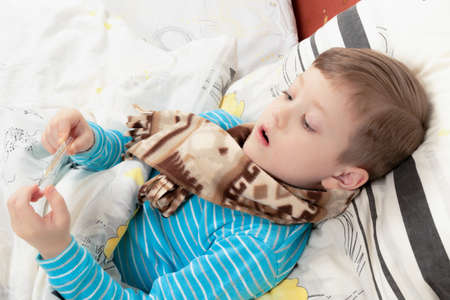 a sick child a boy in a blue jacket lies at home in bed and measures the temperature with a thermometer