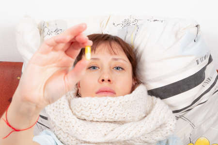 a young pretty girl wrapped in a scarf is ill at home, lies in bed and holds a capsule with medicine in her hand