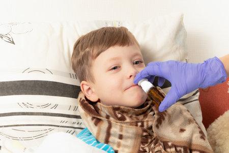 mom in blue medical gloves sprinkles medicine in the nose of a sick child