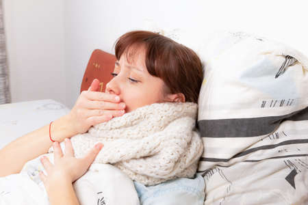 a young pretty girl is sick at home, lies in bed, coughs and holds on to her chest and covers her mouth with her hand