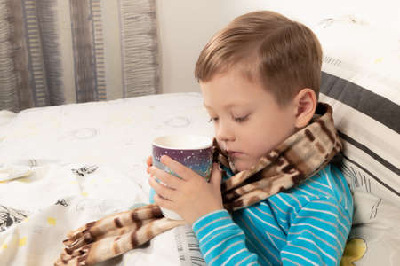 sick child boy in a blue sweater wrapped in a warm scarf in bed drinking ginger tea with honey