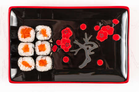 fresh appetizing rolls with salmon in nori seaweed in black-red plates on a white plate. view from above