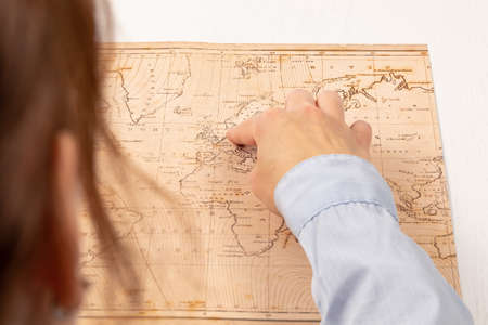 female hand shows the place of travel on the world map on the background of a white wooden table. close-up. selective focus