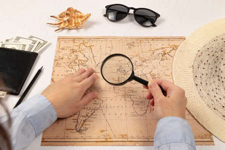female hands hold a magnifying glass over the world map. on a white wooden table lies a black wallet with money, a straw hat, a shell and sunglasses. selective focus