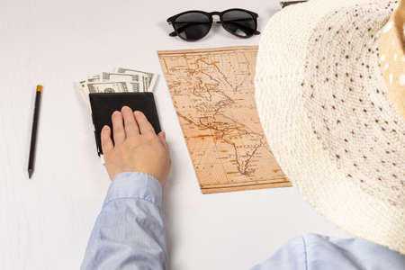 part of a girl in a straw hat. hand holds a black leather wallet with money on a white wooden table sunglasses, world map and diary. selective focus
