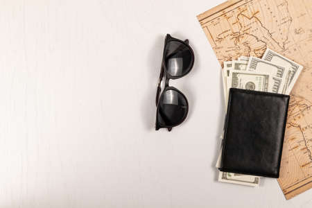 world map, black leather wallet with money and sunglasses on a white wooden table. view from above. flat lay