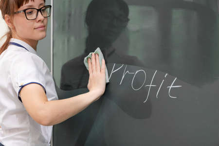 a young woman business coach in a white blouse and glasses wipes the business development graph from the board. close-up Stock Photo