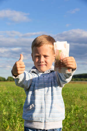 A satisfied preschooler child in a sweater holds paper rubles in nature in a field against the background of a blue sky with clouds. Close-up. Portrait