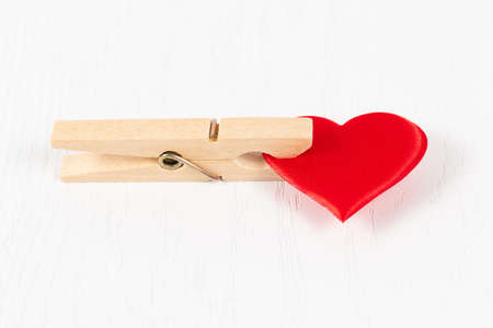red heart clamped in a linen wooden clothespin on the background of a white wooden table. close-up. selective focus