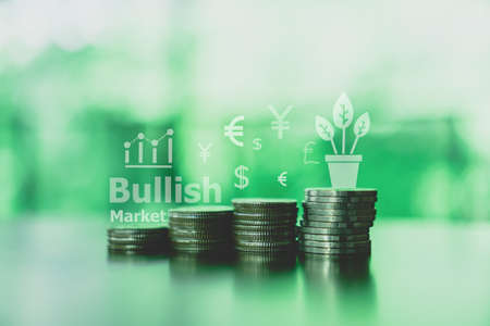 Business financial success concept with currency icon and graph double expose on picture. Gold coins on table and green nature bokeh background.Bullish market situation.
