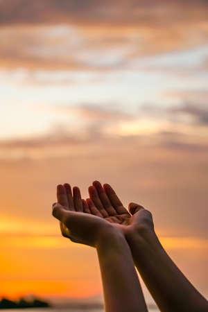 Les mains de la femme se placent ensemble comme prier devant l'océan de la nature et le fond de ciel bleu. Banque d'images