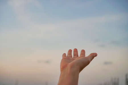 Woman hands reach out to the sky like praying in front of sky background. Imagens