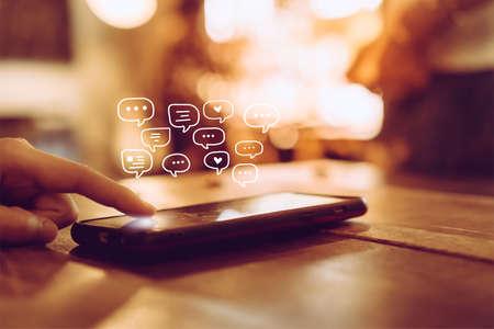 Vrouwenhand met behulp van smartphone-typen, chatten gesprek in chatbox-pictogrammen verschijnen. Social media marketing technologie concept. Vintage zachte kleur Toon achtergrond. Stockfoto