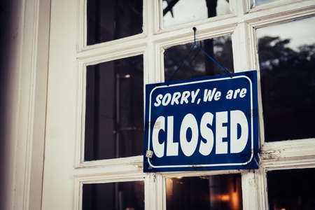 A Sign board of sorry we are closed hang on door of business shop with nature green background Фото со стока - 113372638