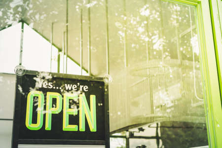 A business sign that says 'Open' on cafe or restaurant hang on door at entrance. Vintage color tone style. Фото со стока
