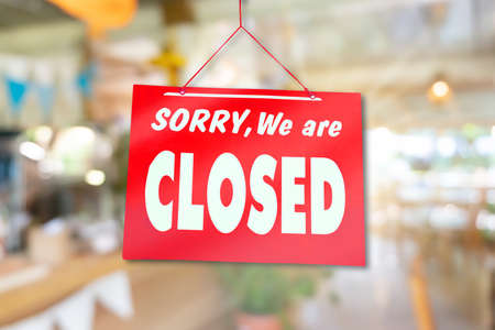 Een bord met sorry dat we gesloten zijn, hangt aan de deur van een bedrijfswinkel met een groene achtergrond van de natuur