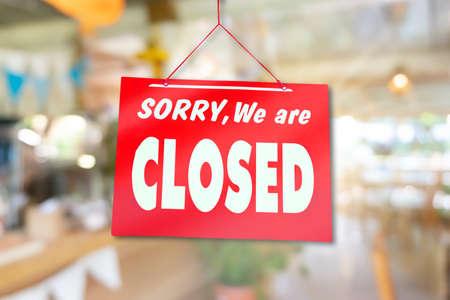 Ein Schild der Entschuldigung, dass wir geschlossen sind, hängen an der Tür des Geschäftsgeschäfts mit Naturgrünhintergrund