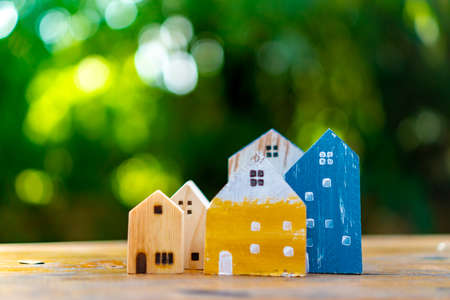 Closed up tiny home model toy on old wood table with sunlight  and green bokeh background. 免版税图像