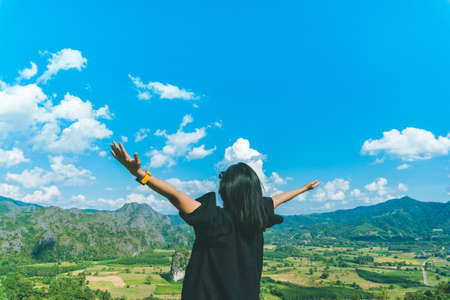 Woman rise hands up to sky freedom concept with blue sky and summer field background. Banque d'images