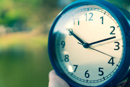 Selective focus of alarm clock with nature bokeh background. 스톡 콘텐츠