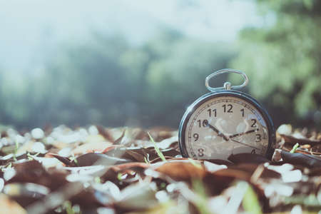 Selective focus of alarm clock with nature bokeh background. Banco de Imagens
