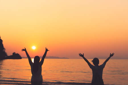 A group of womans rise hands up to sky freedom concept with blue sky and summer beach sunset background.