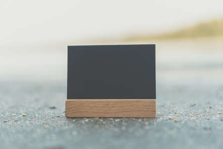 Dark small copy space of blackboard on  sand with beach background.