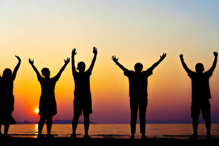 A group of women rise hands up to sky freedom concept with blue sky and summer beach sunset background. Imagens