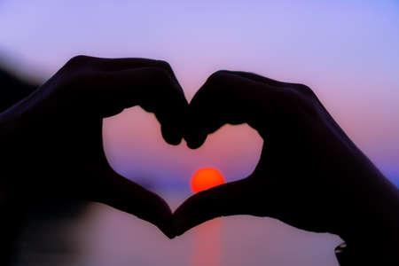 Frauenhand tun Herzform auf tropischem Hintergrund der Sonnenuntergangstrandnatur.