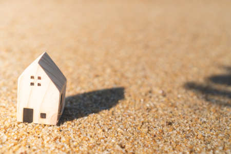 Closed up tiny home models on sand with sunlight and beach background. Stock Photo