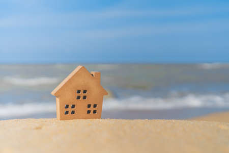 Closed up tiny home models on sand with sunlight and beach background. Archivio Fotografico - 121268168