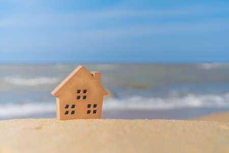 Modelos de casas diminutas cerradas sobre arena con luz solar y fondo de playa.