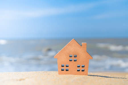 Closed up tiny home models on sand with sunlight and beach background.