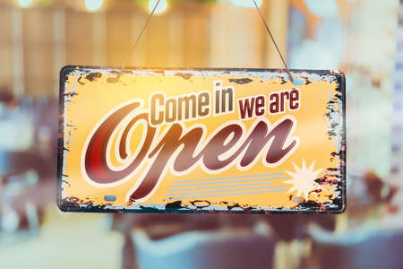 A business sign that says open'on cafe or restaurant hang on door at entrance. Vintage color tone style.