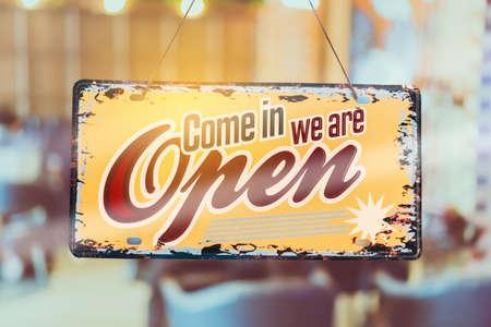 Un cartello aziendale che dice aperto su un bar o un ristorante appeso alla porta all'ingresso. Stile di tono di colore vintage.