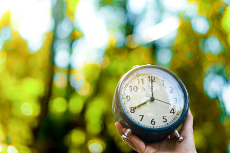 Selective focus of alarm clock with nature bokeh background. Stock Photo