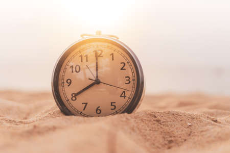 Selective focus of alarm clock on sand  with nature bokeh beach background. Time in life concept Stock Photo - 125125840