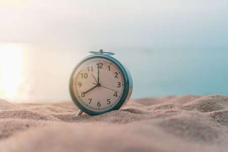 Selective focus of alarm clock on sand  with nature bokeh beach background. Time in life concept