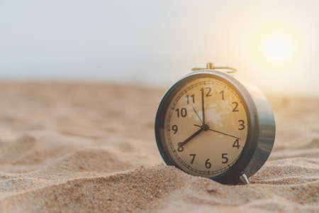Selective focus of alarm clock on sand  with nature bokeh beach background. Time in life concept Stock Photo - 125120478
